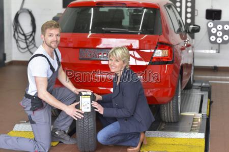 portraet des laechelnden automechanikers mit kunden