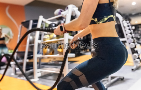 young woman doing battle rope exercise
