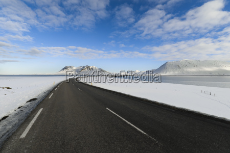 empty road through iceland with mountains