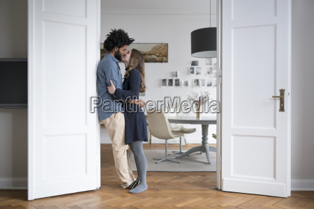 kissing couple at home standing in