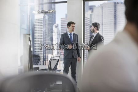 two businessmen talking in city office