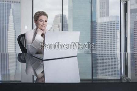 smiling businesswoman sitting at desk in