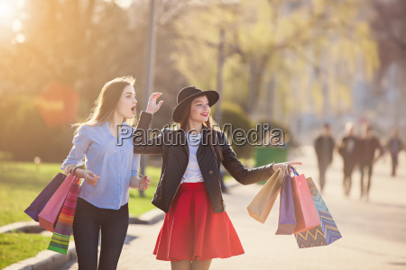 two girls walking with shopping on