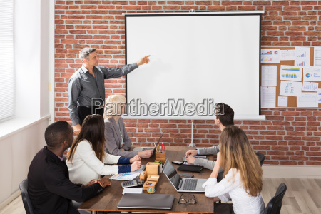 mature businessman giving presentation in meeting