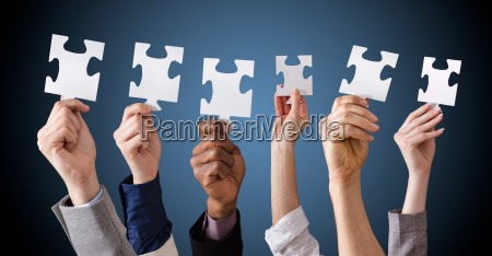 businesspeople holding puzzles in hands