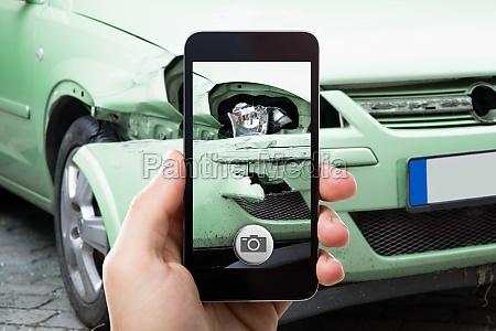 person die foto des autounfalls nimmt