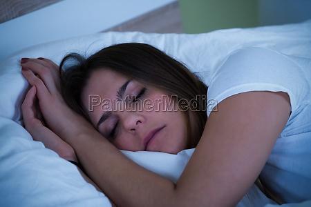 blonde woman sleeping on bed