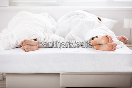couples feet on bed
