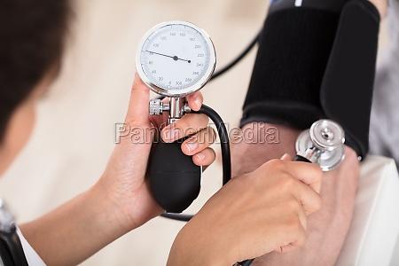 doktor misst ihren blutdruck