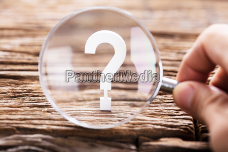 question mark sign through magnifying glass