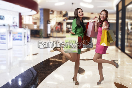 happy two young asian woman holding