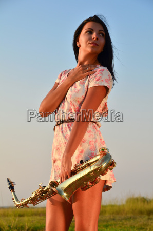 beautiful girl holding a saxophone in