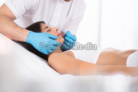 cosmetologist applying permanent make up on