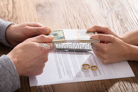 couples hand holding currency over the