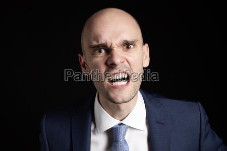 businessman aggressively shows teeth