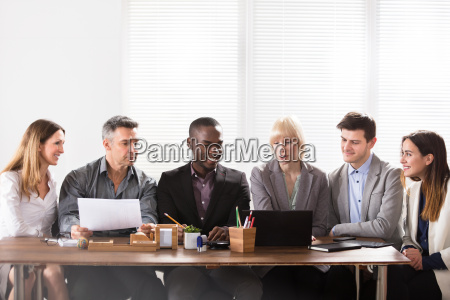 businesspeople looking at laptop