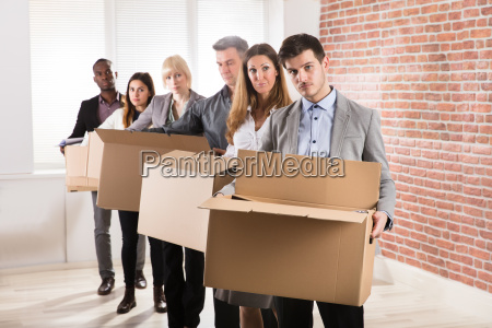 reihe von geschaeftsleuten standing mit kartons