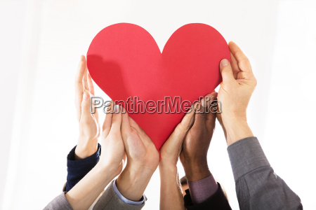 businesspeople holding red paper heart
