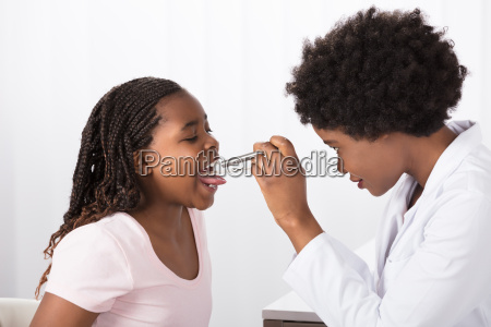 doctor checking his patients throat