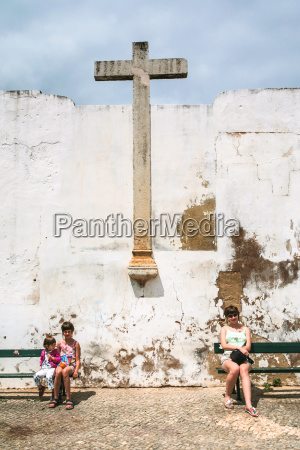 tourists near old medieval cross in