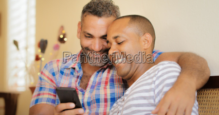 happy gay couple looking at pictures