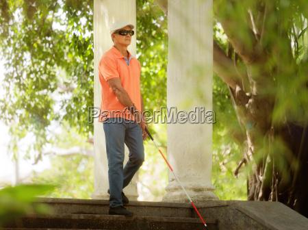 blind man walking and descending steps