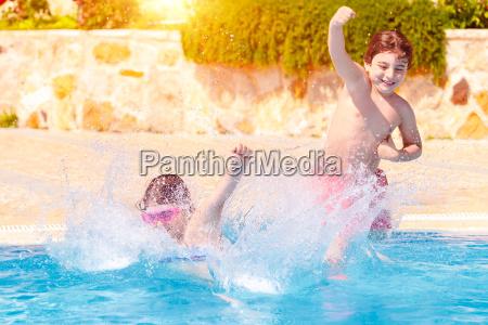 zwei glueckliche kinder im pool