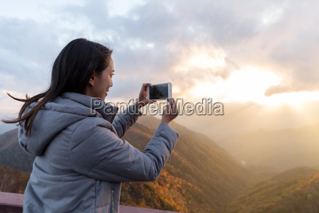 young woman taking photo on cellphone