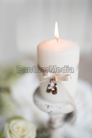 burning candle with wedding rings