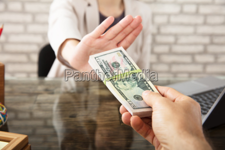 businesswoman refusing to take bribe from