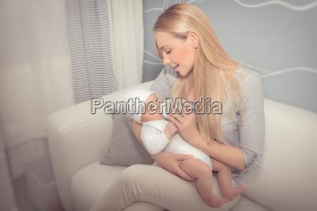 glueckliche mutter fuettert ihr baby