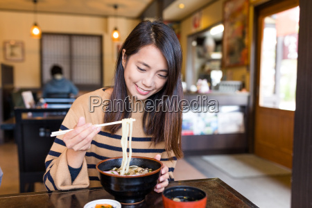 young woman eating japanese udon in