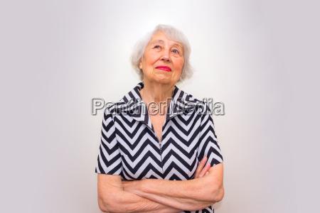 portraet einer traeumenden seniorin die mit