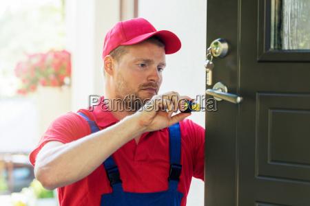 locksmith in red uniform installing new