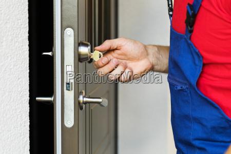 repairman working with house door lock