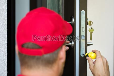 door lock service locksmith working