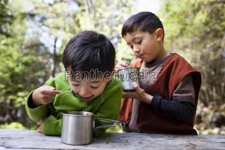 two boys eating from metal mugs