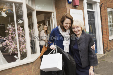 two women with shopping bags hugging