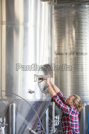 male brewery worker checking fermentation process