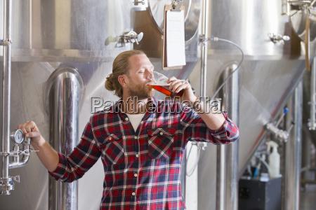 male brewery worker tasting beer sample