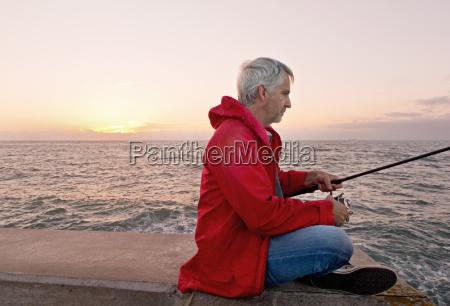 mature man sea fishing from jetty