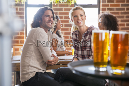 waiter serving young couple meeting for