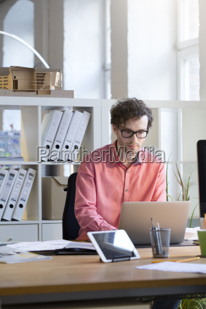 man using laptop at desk in