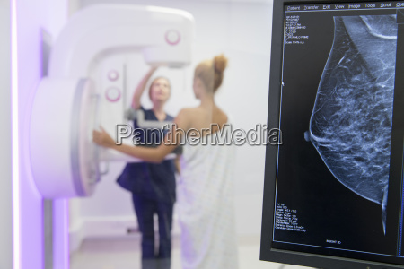 hospital radiographer giving mammogram to female