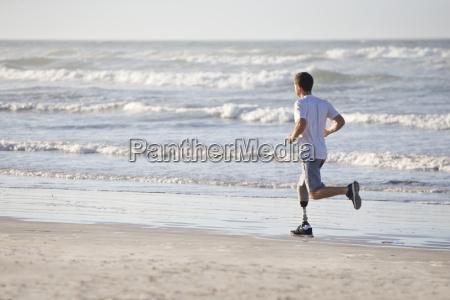 man with artificial leg running along