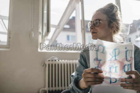 young woman holding letter templates looking