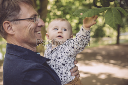 smiling father holding baby boy at