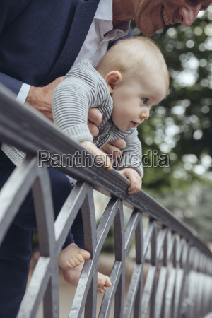 father holding his baby to look