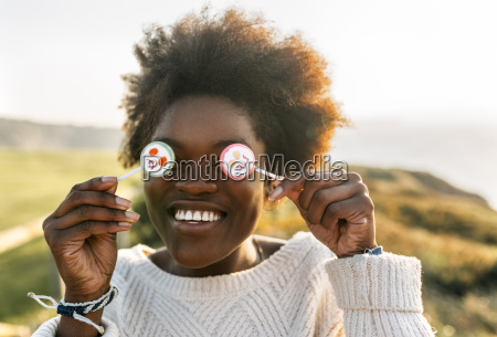 young woman having fun with lollipops