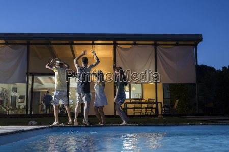 four happy friends dancing at poolside
